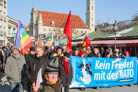 Munich, Germany - February 7, 2015: Peaceful anti-NATO social protest march against the aggressive policy USA in Europe and presence army North Atlantic Alliance military forces.