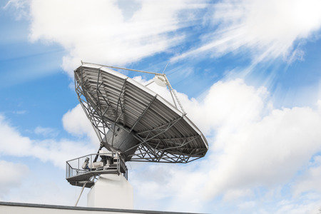 bidirectional: Telecommunications radar parabolic radio antenna as part of global communication technology stations system against sunny sky with sun rays sunbeams. Toned and filtered stock photo.