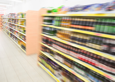 store interior: Long shelves with beverages bottles in big grocery food store in supermarket. Filtered stock photo blurred in motion.