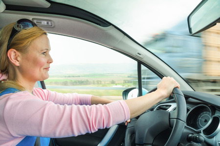 Attractive adult woman safe and carefully driving car on suburban road. Inside the auto photo with high speed oncoming lorry truck blurred in motion. Stock Photo