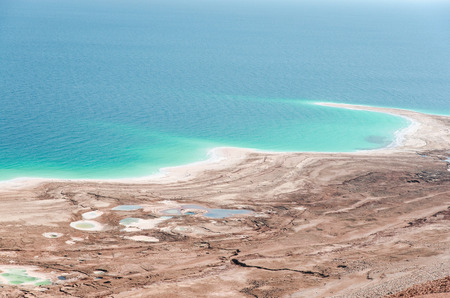 shrinking: Natural environmental disaster on Dead Sea shores. Water level decreases and surface rapidly shrinking due to human activity. Stock Photo