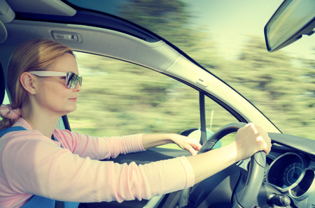 processing speed: Smiling beautiful woman in sunglasses driving at high speed car with panoramic windshield. Cross processing filtered and split toned internal stock photo with low shutter speed and blurred in motion natural background.