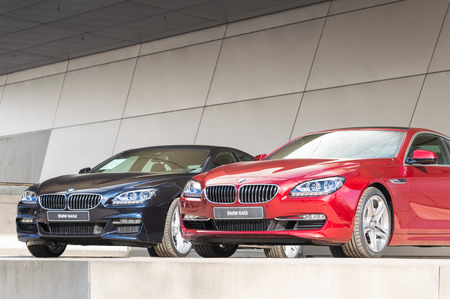 lineup: MUNICH, GERMANY - APRIL 12, 2014: New modern BMW 640 model lineup of first class exclusive business sedan cars. Front view of dark blue 640d and red 640i.