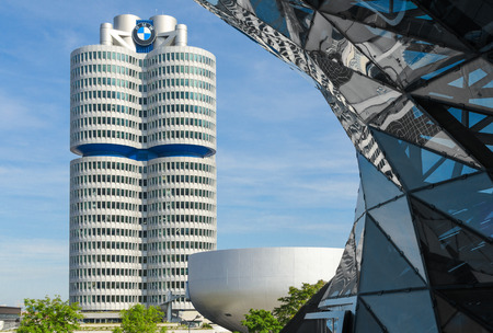 automaker: Munich, Germany - September 28, 2014: BMW four-cylinder tower is a Munich landmark which serves as world headquarters for the Bavarian automaker. Stock photo with elements of designs of BMW Museum and BMW Welt (world). Editorial