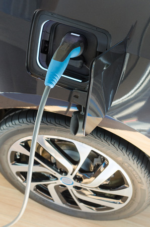 Modern electric ecologically pure car plugged in to power supply at charging station