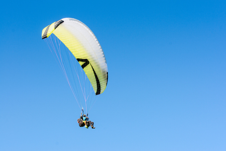 Paragliding action adventure sport flight on soaring wing in height of clear blue sky