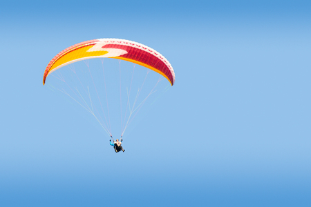 Tandem: Tandem paraglider free gliding at high altitude in deep blue sky Stock Photo