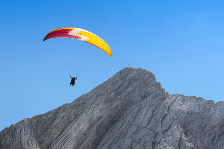 Paraglider free soaring at a great height in cloudless sky over dolomites Alps peak mount Stock Photo