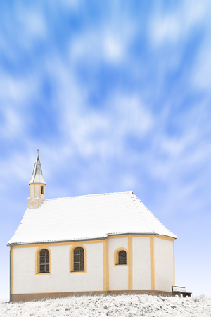 snowbound: Tiny winter church or single snowbound small chapel vertical stock photo with blured in motion clouds in blue sky