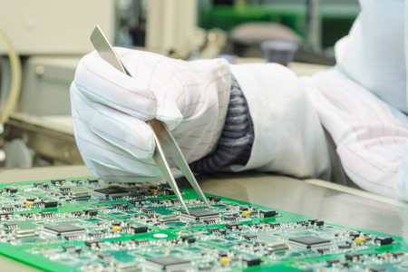 Quality control and assembly of SMT printed components on circuit board in QC lab of PCB manufacturing high-tech factory Standard-Bild