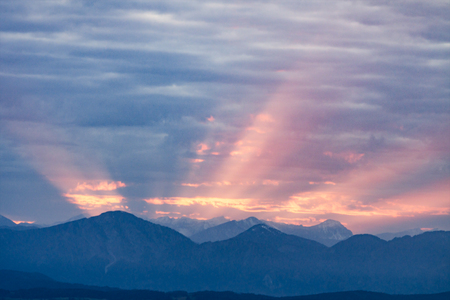 dawning: First rays of the rising sun on dawning cloudy sky over dark blue morning Alps mountains Stock Photo