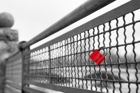 white color: Red love lock padlock with heart on bridge symbol of true eternal love and commitment. Black and white stock photo with selective color effect.