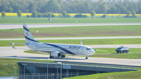landed: Munich, Germany - May 6, 2016: Airplane Boeing 737-800 by El Al Israel Airlines carrier landed in international airport and escorted by armed police armored vehicle provides anti terrorism attack security measures.
