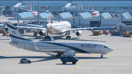 ensuring: Munich, Germany - May 6, 2016: Aircraft Boeing 737-800 by Israeli airline El Al taxiing to airport terminal with escort armored vehicle ensures antiterrorism force protection