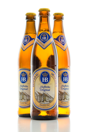 Munich, Germany - June 11, 2016: The three bottles of cold light original lager beer from Bavarian Hofbrau Munich brewery. Backlit and isolated on white stock photo.