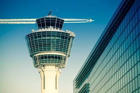便管理航空管制塔と澄んだ空に飛行機が飛んでミュンヘン国際空港の旅客ターミナル。調子を整える効果を分割ストック フォト。