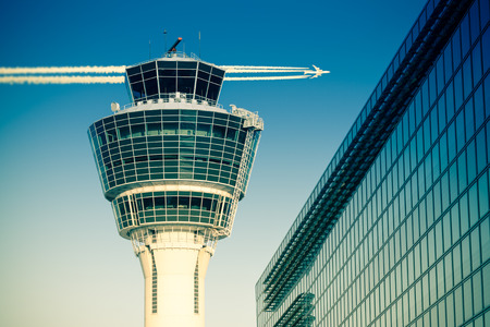 항공편 관리 항공 컨트롤 타워와 여객 터미널 뮌헨 국제 공항에서 비행기를 비행하는 맑은 하늘. 분할 토닝 효과와 재고 사진입니다.