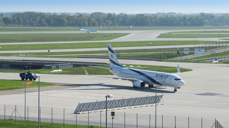 Munich, Germany - May 6, 2016: Israeli airline El Al plane landed in international airport and taxiing from runway to terminal accompanied by security armored vehicle.