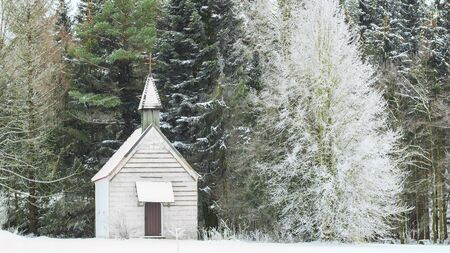 Peaceful winter view of little snow-capped rural wooden church on snowfield glade in frozen forest Stock Photo