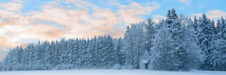 Panoramic landscape of snowbound forest with frosty small church unter morning sunrise cloudy sky
