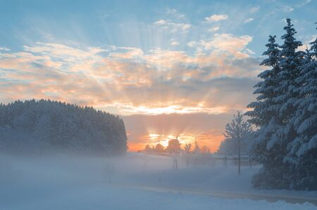 Winter morning snowy tranquil rural scenery with fog over snowbound forest and dawn sunlight rays breaking through clouds Stock Photo