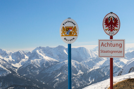 State boundary between Germany and Austria on top of Alpine mountain ridge. Sgnboards with the coat of arms of free state Bavaria and Tyrol and words Warning: National Border.