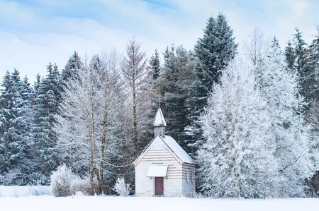 Small wooden chapel on snowbound frosty glade in snowy frozen forest. Winter wonderful scenery in German Bavarian region Allgaeu at the foot of Alps. Stock Photo