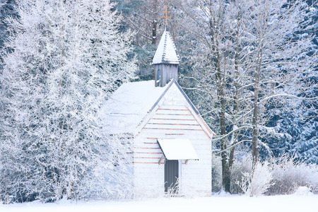 Small woody chapel in frozen snowy forest. Stock photo captured in Bavarian Alpine rural region Allgaeu.