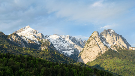 Snow-capped Alpspitze mount peak is part of tectonics limestone Alps mountains ridge in Bavaria Germany. Springtime morning panoramic scenic view stock photo captured from Garmisch-Partenkirchen side.