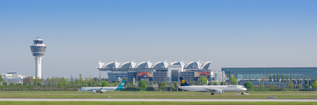 Munich, Germany - May 6, 2016: Panoramic view of Munich international airport with passenger terminal, traffic control tower and taxiing on taxway airplanes