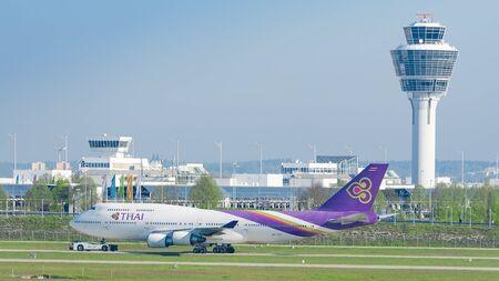 747 400: Monaco di Baviera, Germania - 6 maggio 2016: linea del jet Boeing 747-400 della Thai Airways compagnie aeree internazionali rullaggio sulla pushback rimorchiatore all'aeroporto internazionale di passeggeri di Monaco di Baviera Editoriali