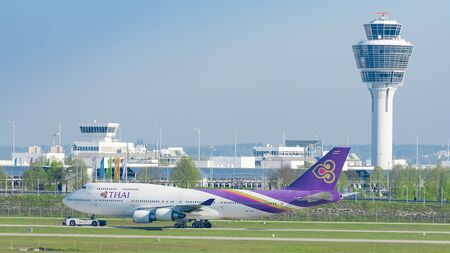 turbojet: Munich, Germany - May 6, 2016: Jet airliner Boeing 747-400 of Thai Airways International airlines taxiing on pushback tug at Munich international passenger airport