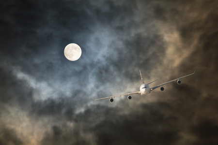Passenger jet airliner makes non-stop night flight in the light of full moon to long-haul and long-range destination through storm clouds in turbulence conditions Stock Photo