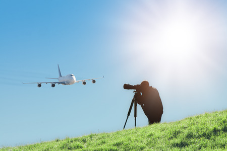 Silhouette of spotter photographer with camera and telephoto lens capturing photos of landing airliner. Aircraft or plane spotting is a hobby of tracking and monitoring the airplanes which is often accomplished by photography. Stock Photo
