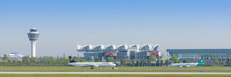 Munich, Germany - May 6, 2016: Panoramic view of Munich international airport with taxiing passenger airplanes and terminal and air traffic control tower Editorial