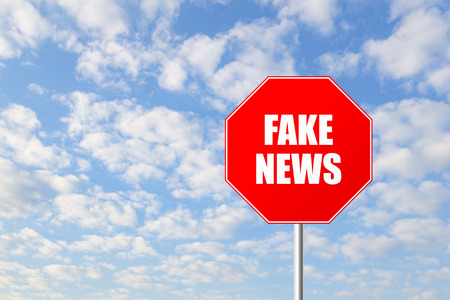 deceitful: Stop fake news road sign against blue sky