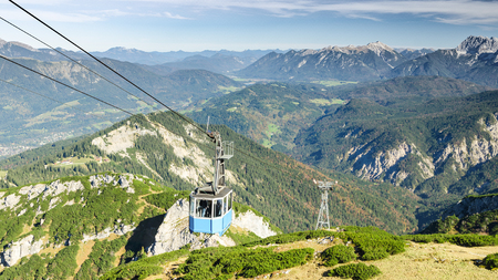 Aerial cableway gondola lifts tourists to top of Alpspitze mountain in Bavarian Alps