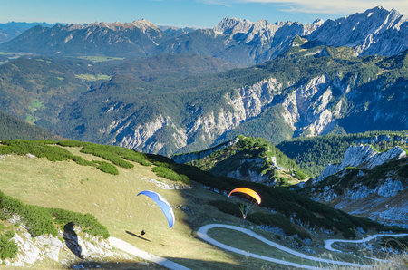 Pair paraplanes launching and soaring in Bavarian Alps mountains. Stock photo with aerial view on Alpine landscape.