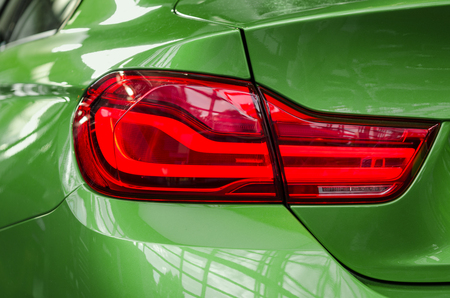 Close-up sports car rear tail-lamp with brakelight stop signal