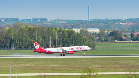 Munich, Germany - May 6, 2016: Passenger plane of Air Berlin low-cost airline touching down runway with smoke in Munich international airport