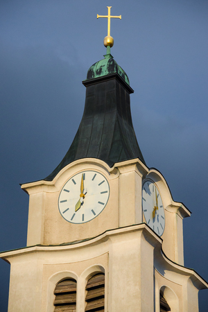 Old historical belfry bell tower with antique clock and golden cross on the top of church
