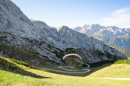 Alpine landscape with hovering paraglider in Bavarian Alps mountains