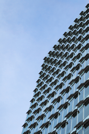 Glass and steel modern high-rise office building with open ventilation system in hot day