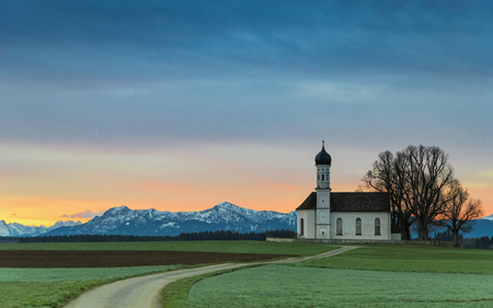 Sunrise over old chapel in green field with Alps mountains on background Standard-Bild