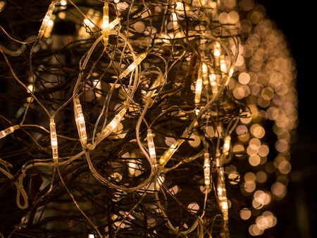 Bright lights of Christmas electric garland with bokeh on trees. Close-up outdoors stock photo.