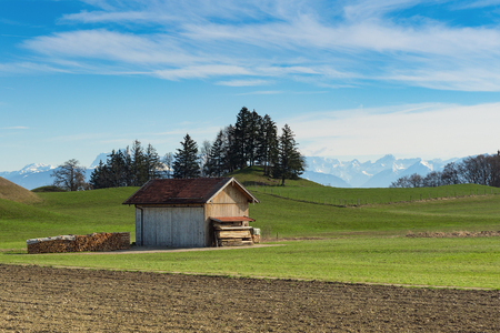 Alpine mountains spring landscape with sunny green grassland field and wooden shed Standard-Bild