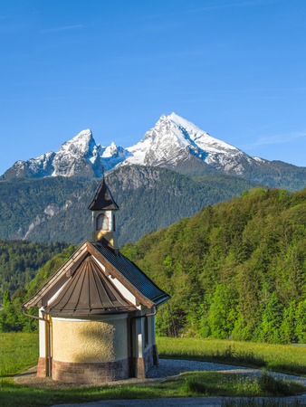 Vertical view of small chapel and snowy summit of Watzmann mountain in Bavarian national park Berchtesgaden Standard-Bild - 93508396