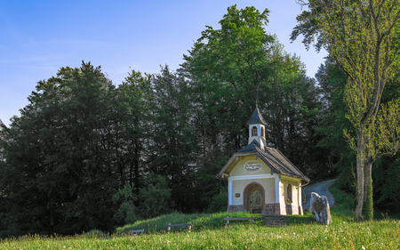 Small chapel on the hill in Berchtesgaden Bavarian national park. Panoramic stock photo with morning sunlight spring fresh greenery.
