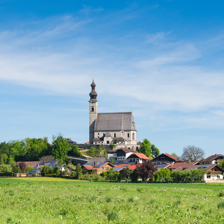 Spring scenery with rural Catholic church and small Bavarian village. Square stock photo.