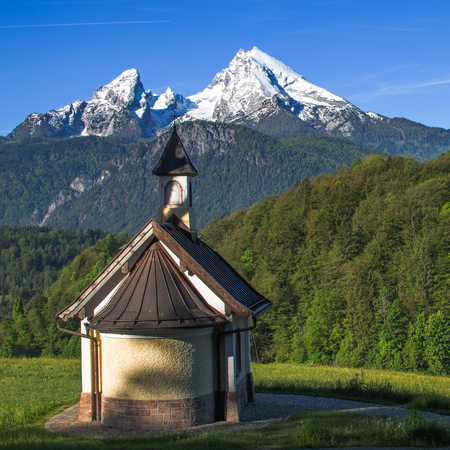 Small chapel Kirchleitn and snow-capped summits of Watzmann mountain. Square stock photo captured in German national park Berchtesgaden.